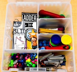 This bin can be bought on Amazon, and has great compartments to keep this game's materials organized.