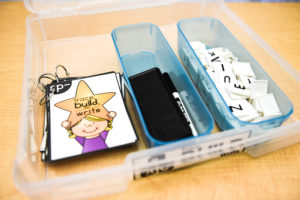 What's in the box of the Trace, Build, Write Phonics Game: cards, a dry erase marker, bananagrams letters, and a dry eraser