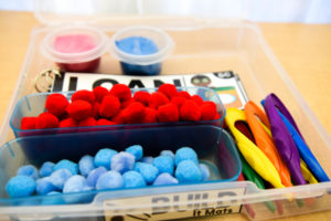 Blue and red pom poms, blue and red clay, word cards and plastic tweezers for the I Can Build It Phonics Game