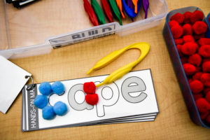 Students can use tweezers to select pompoms to fill the letters of each word card. They should color code to identify sound-spelling letters.