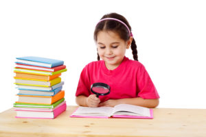 Young student using a magnifying glass to read a book, next to a stack of books